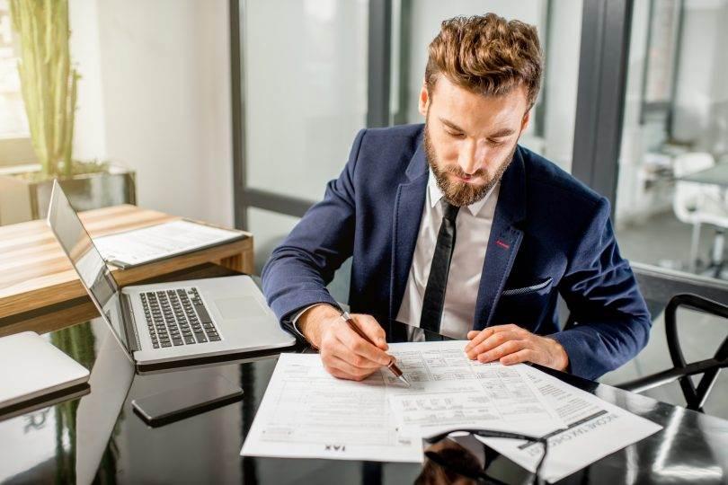 hombre-revisando-papeles-trabajando-trade-marketing-manager
